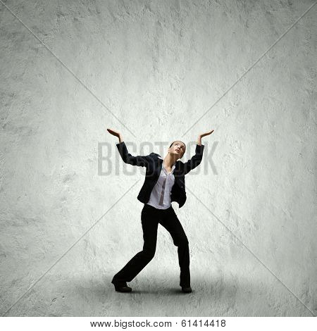 Young businesswoman holding some burden above head