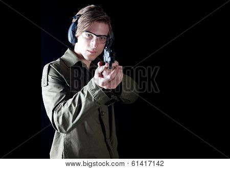 Man aiming a hand gun wearing protective gear poster