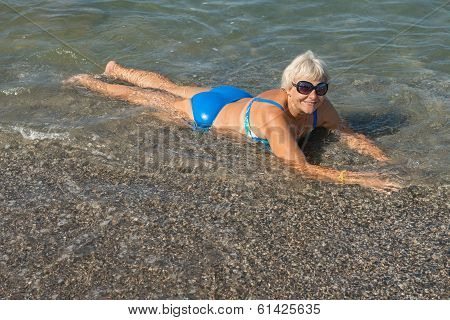 Aged Lady Is Lying On Water Edge At The Sea Beach.