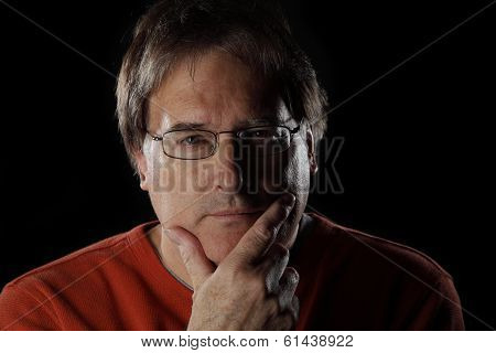 Mature man looks quizzical or thoughtful with his hand on his chin - on black background with dramatic lighting poster