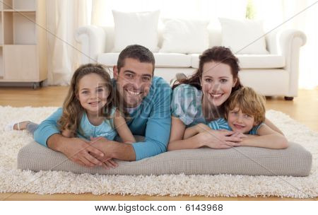 Happy family on floor lying in living-room poster
