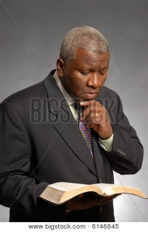 African American man reading and studying the bible poster