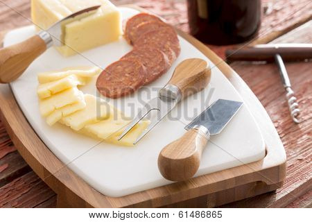 Harvati cheese with sliced spicy sausage served on a cheeseboard with cheese cutters alongside a bottle of red wine with a corkscrew poster