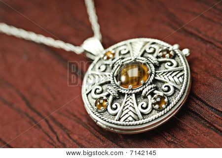 Celtic Siver And Amber Locket on red silk. poster