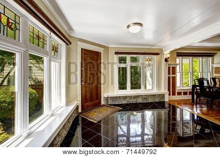 Luxury interior. Foyer with black shiny tile floor large windows with stone windowsill base trim poster