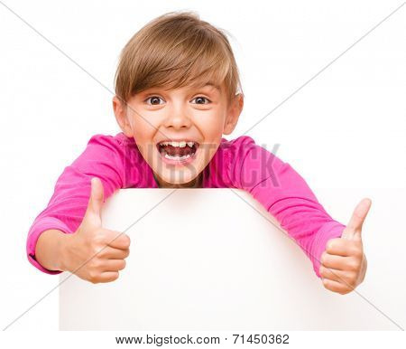 Little girl is looking out from the blank banner showing thumb up sign, isolated over white