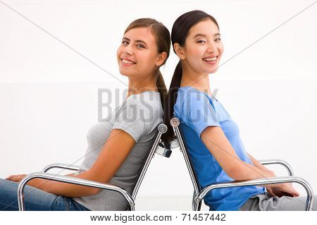 Two Happy Businesswoman Sitting In Chairs To Back