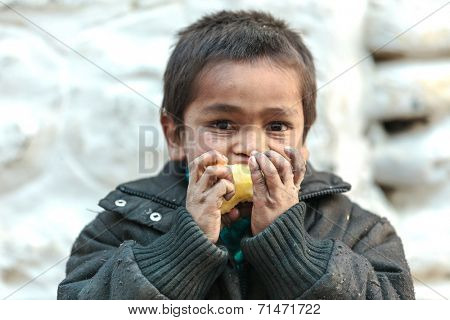 MUKTINAH, NEPAL, NOVEMBER 10, 2010 : Poverty in Nepal, a starving kid is eating an apple  in the small mountain village of Muktinah, Annapurna, Nepal.