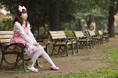 Japanese girl in lolita cosplay fashion sitting on a bench, Tokyo poster