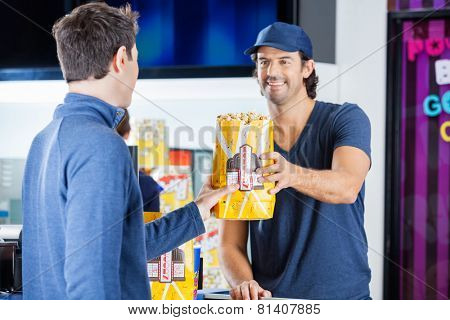 Smiling male worker selling popcorn to man at cinema concession stand