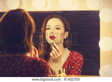 Portrait of a beautiful woman as applying makeup near a mirror. Photo in retro color style. poster