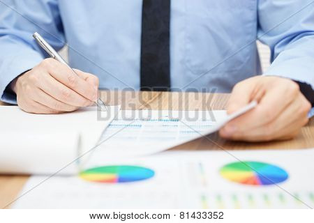 Bussinessman examines data and numbers and finalizing report poster