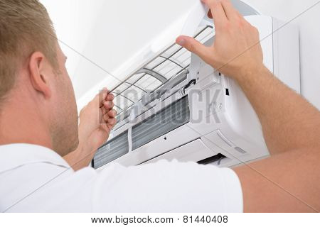 Portrait Of A Young Man Adjusting Air Conditioning System poster