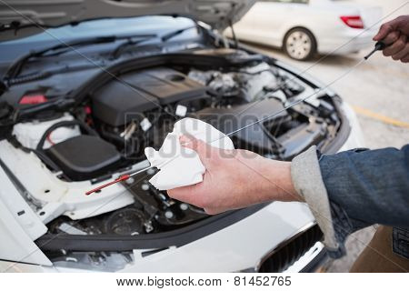 Close up of man checking car engine oil in a car park