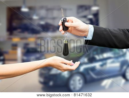auto business, car sale, transportation, people and ownership concept - close up of car salesman giving key to new owner or customer over auto show background