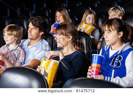 Families having snacks while watching movie in cinema theater