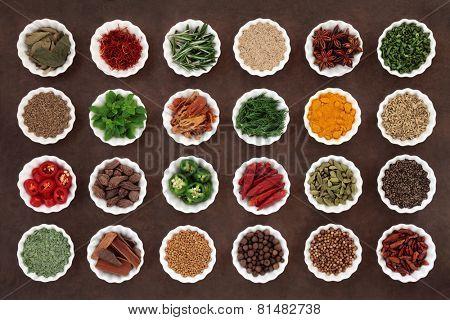 Large herb and spice collection in porcelain crinkle bowls over lokta paper background.