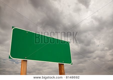 Blank Green Road Sign Over Storm Clouds