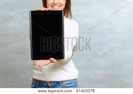Smiling woman showing her tablet.