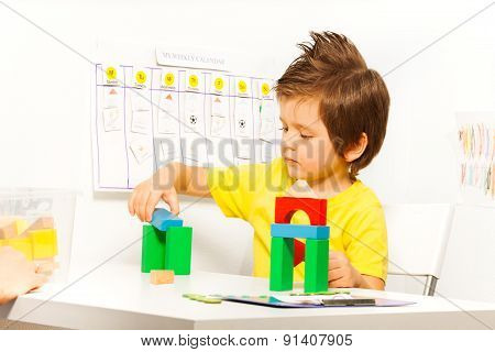 Boy putting colorful cubes in construction game
