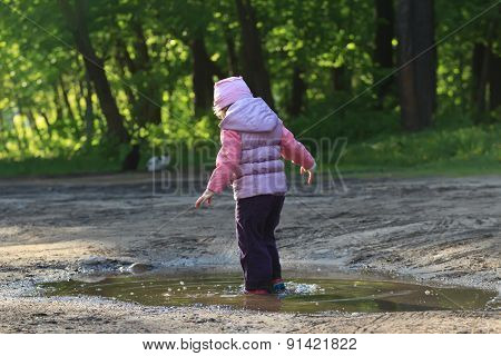 Curious toddler girl walking in summer puddle