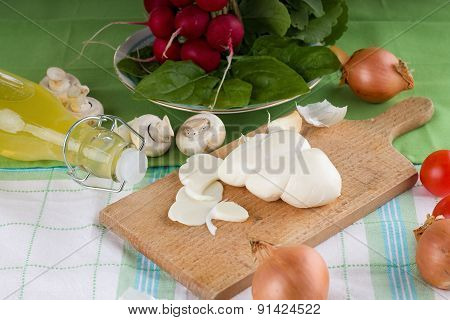 Horizontal photo of traditional twisted slovak cheese on cutting board plus various vegetable around as onions garlics mushrooms and radishes with baby spinach and bottle with lemonade. All is placed on green cloth. poster
