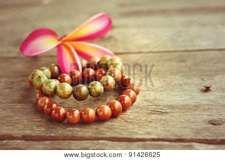 Stone Bracelet with pink frangipani flowers on wooden background. poster