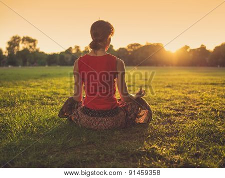 Woman Meditating In Park At Sunset