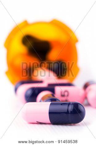 Medicine in front of an open prescription bottle