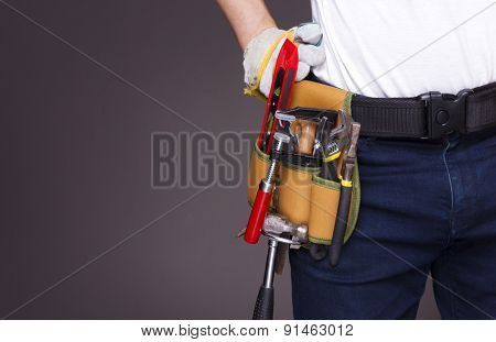 Worker with toolbelt and against dark background