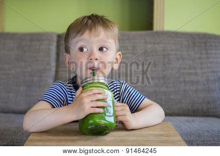 Little Boy Drinking A Green Smoothie