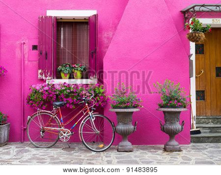 Burano, Italy - 21 May 2015: Painted Building With Bicycle In Front.