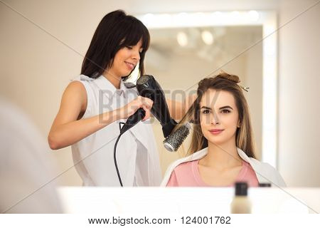 Almost done. Pleasant positive professional hairdresser holding hairdryer and drying hair of her client while working in the hairdressing salon