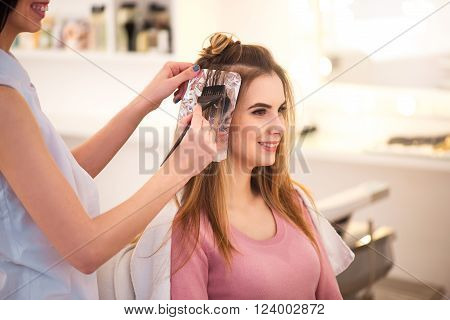 Waiting for result.  Beautiful charming woman sitting in the hairdressing salon while professional hairdresser dyeing her hair