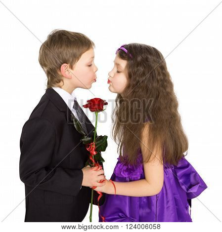 Kids love concept. Little boy and girl kissing and holding rose flower. Isolated on white background.