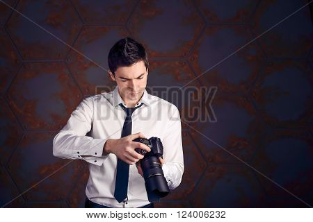 Professional photographer scrolls photos om his camera