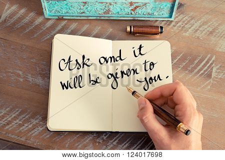 Retro effect and toned image of a woman hand writing on a notebook. Handwritten quote Ask and it will be given to you as inspirational concept image