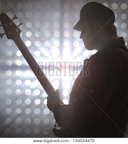 Bassist playing bass guitar in smoke. backlight