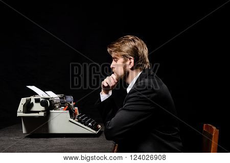 writer a man in a black jacket typing on typewriter on a black background