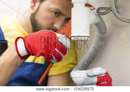 plumber fixing the sink siphon in a bathroom or kitchen poster