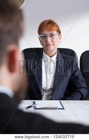 Older bossy woman in suit in corporation talking with young applicant