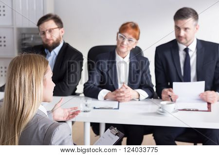 Young pretty intern talking with three bossy businesspeople to work in company