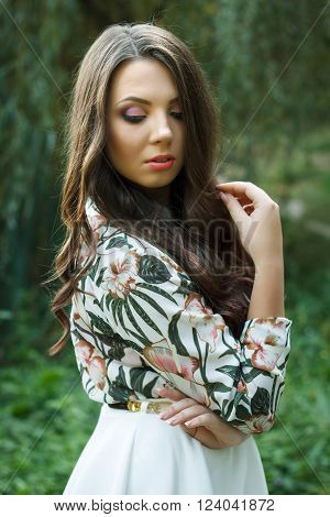 Portrait of beautiful brunette woman poses on green background outdoors