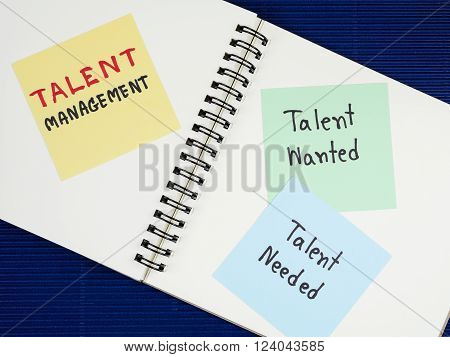 Handwriting Talent Management, Talent Needed, Talent Wanted on colorful note paper and notebook with blue paper background.