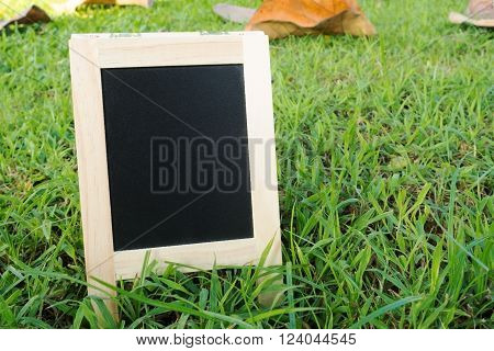 Small wood A-frame blackboard with blank area for text on fresh green grass field. Wooden black board with blank area for message.