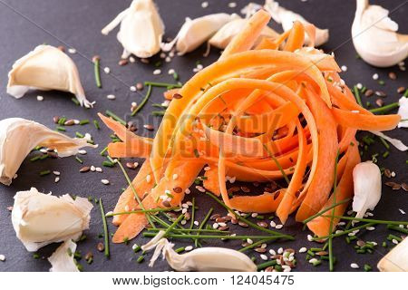 Horizontal photo with heap of several carrot shavings. Spilled sesame and flux seeds are around with chopped green chive and garlic. All is placed on black slate board.