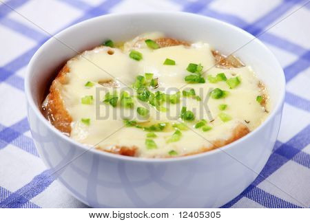 A picture ofa bowl of fresh french onion soup baked with toast and cheese poster