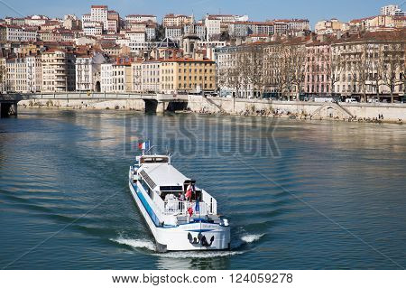 Lyon France - March 26 2016: Boat moving down the Saone river in the city of Lyon.