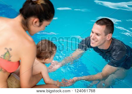 Introduction to water - Baby entering swimming pool for the first time.