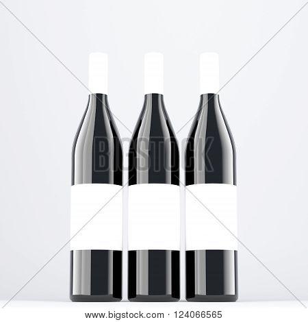 Three wine bottles aranged in line, blank labels on them. Dark glass. Concept of bottling wine. Mock up. 3D rendering.